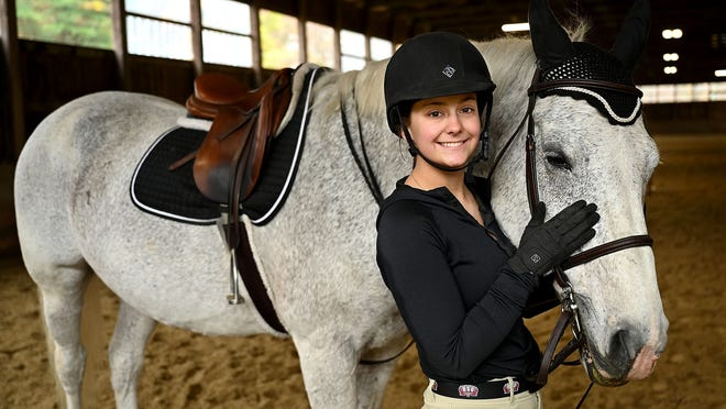 "Katherine Ryan, 20, of Mendon, with her 17-year-old Irish sports horse ""Max"" at Singing Winds Farm in Uxbridge on Thursday, Oct. 29. Ryan is a junior at Bridgewater State University and competes on the equestrian team."