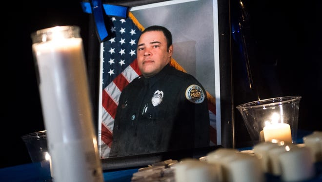 A photo of Officer Eric Mumaw sits on a table during a vigil for Metro Nashville Police Department Officer Eric Mumaw at Peeler Park in Madison, Tenn., Friday, Feb. 3, 2017. Mumaw died in the line of duty Thursday while attempting to rescue a woman in the Cumberland River.