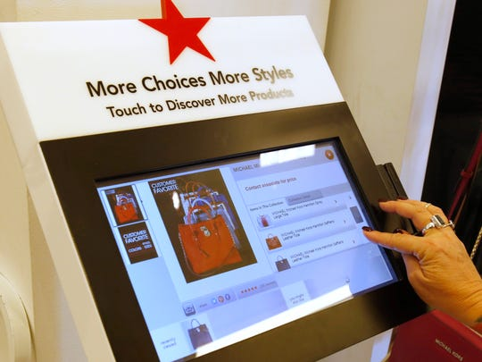 "Chrissie Goodwin, a Michael Kors specialist at the Kenwood Towne Centre Macy's store demonstrates the use of a ""Point of Purchase"" (POP) machine. The retailer has installed several POP screens at the Kenwood store."
