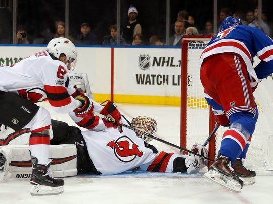 New Jersey Devils goalie Keith Kinkaid (1) blocks a shot by New York Rangers center Kevin Hayes (13) as New Jersey Devils defenseman Will Butcher (8) helps defend during the second period of an NHL hockey game game, Saturday, Oct. 14, 2017, in New York. (AP Photo/Julie Jacobson)