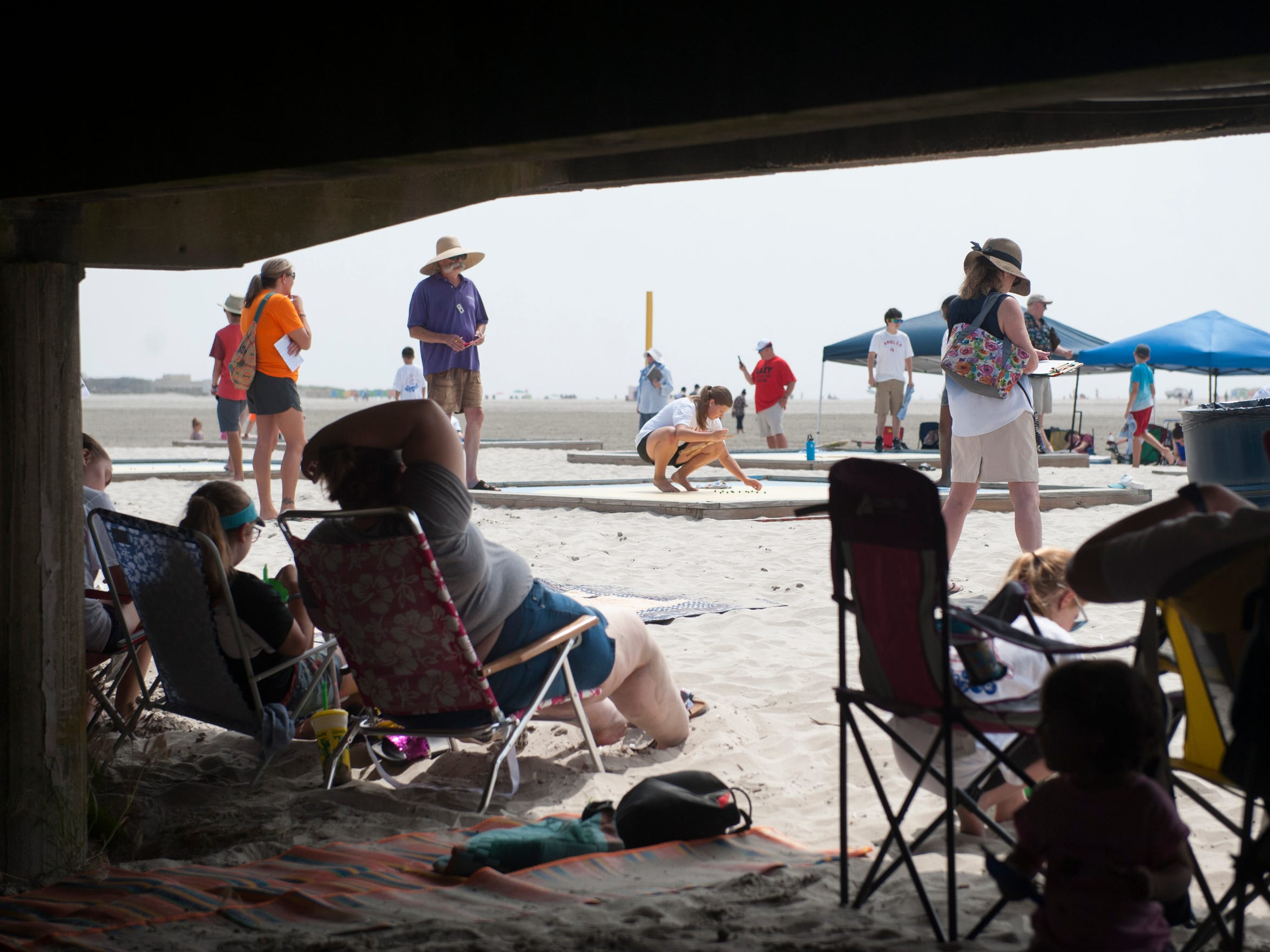 Spectators sit under the boardwalk to take refuge from the sun and heat as they watch the National Marbles Tournament in Wildwood on Monday, June 18, 2018.
