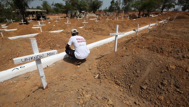 A man crouches next to the grave of an unknown man at the National Memorial Cemetry on Disco Hill, Margibi County, Liberia. The cemetery was established to provide a dignified burial for ebola victims and bring an end to the usual cremation of victims during the outbreak.