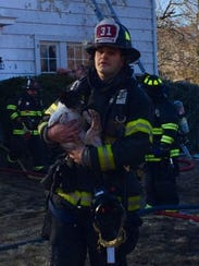Port Chester Lt. Sam Sciavillo is seen carrying a dog