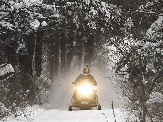 A snowmobile travels a newly groomed trail in East Montpelier in 2012.