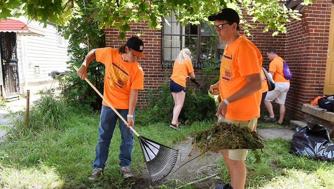 Austin Colon, 17, left, and Charlie Neuendorff, 18, right, both from St. Paul Lutheran Church in La Grange, Texas, rake up and shovel away weeds on Lawton Street not far from the Focus: HOPE campus in Detroit on July 16, 2015.