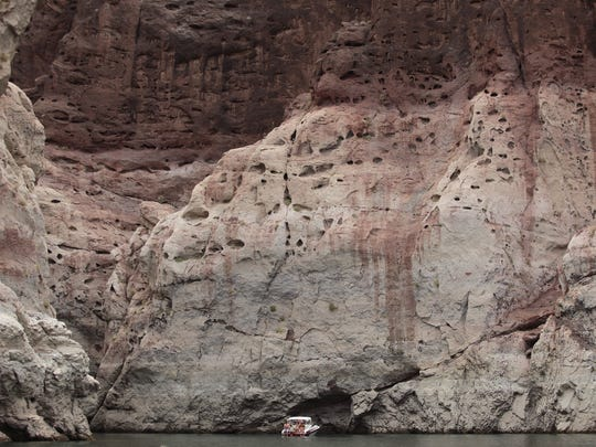 """A pleasure boat cruising near the steep canyon walls of Lake Mead on May 23. The boat is dwarfed by the """"bathtub ring"""" that shows the reservoir's high-water mark."""