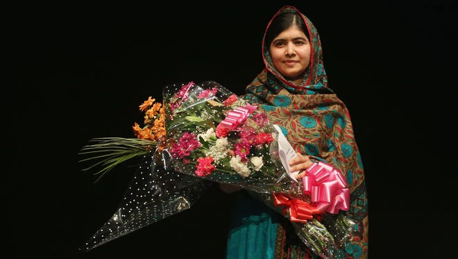Malala Yousafzai holds a bouquet of flowers, given to her on behalf of the Pakistani Prime Minster during a press conference at the Library of Birmingham after being announced as a recipient of the Nobel Peace Prize, on October 10, 2014 in Birmingham, England. The 17-year-old Pakistani campaigner, who lives in Britain where she received medical treatment following an assassination attempt by the Taliban in 2012, was jointly awarded the Nobel peace prize with Kailash Satyarthi from India. Chair of the Nobel Committee Thorbjorn Jagland made the announcement in Oslo, commending Malala for her ?heroic struggle? as a spokesperson for girls' rights to education.