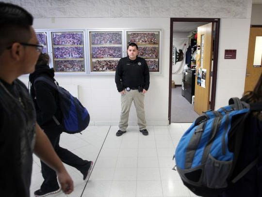 Ignacio Enriquez Jr., a school resource officer at Appleton North, stands in the hallway while students move to their next class Friday, Dec. 11, 2015, in Appleton