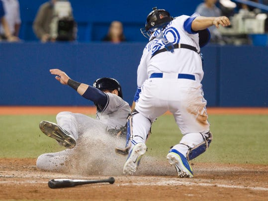 Toronto Blue Jays catcher Dioner Navarro tags out New York Yankees' Jacoby Ellsbury at home plate during the ninth inning of a baseball game Friday, Aug. 29, 2014, in Toronto. (AP Photo/The Canadian Press, Fred Thornhill)