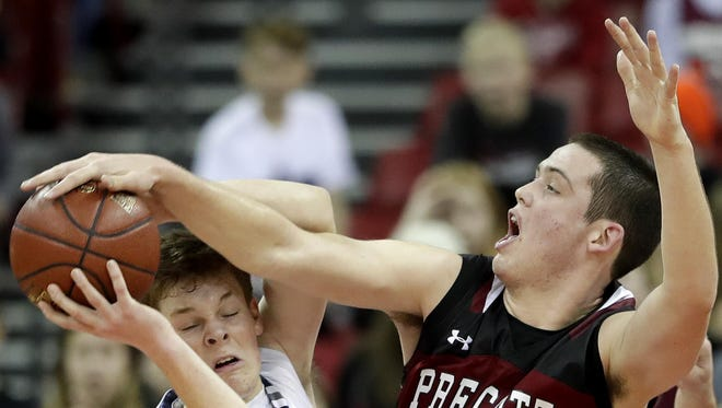 Xavier's Nate DeYoung, left, has a shot blocked by Owen Hamilton during Saturday's game in Madison.