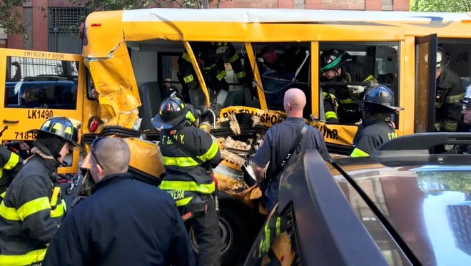 In this Tuesday, Oct. 31, 2017 photo provided by Sebastian Sobczak, emergency personnel work on a school bus after a driver rammed into it in New York.