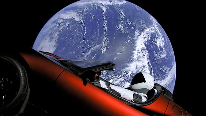 "This image from video provided by SpaceX shows Elon Musk's red Tesla sports car with a dummy driver named ""Starman"" which was launched into space during the first test flight of the Falcon Heavy rocket on Feb. 6, 2018."