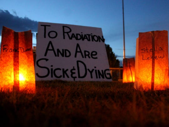 In this 2016 file photo, signs were placed behind luminarias at the Tularosa Basin Downwinders candlelight vigil.