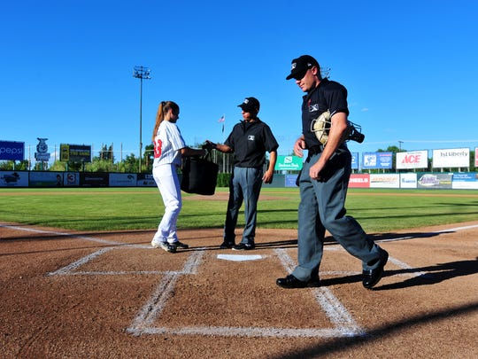 Voyagers bat girl Sarah Faulk receives the bag of game balls from the umpires before the start of Wednesday night's game against the Orem Owlz at Centene Stadium.