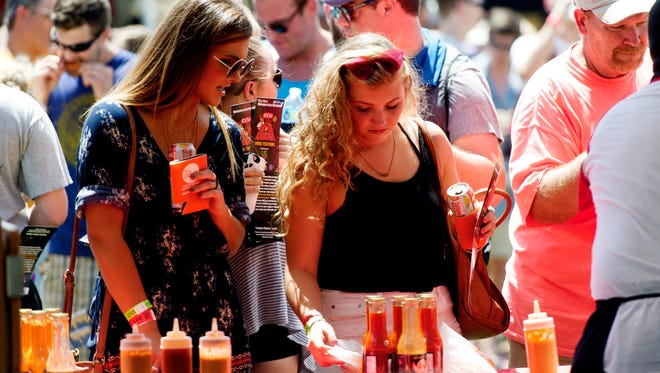 Visitors select from a menu of wings at the annual Big Kahuna Wing Festival in World's Fair Park in Knoxville, Tennessee on Saturday, June 17, 2017. Between 8,000 to 10,000 people attended the event, which featured 38 teams competing for a grand prize of $4,000.