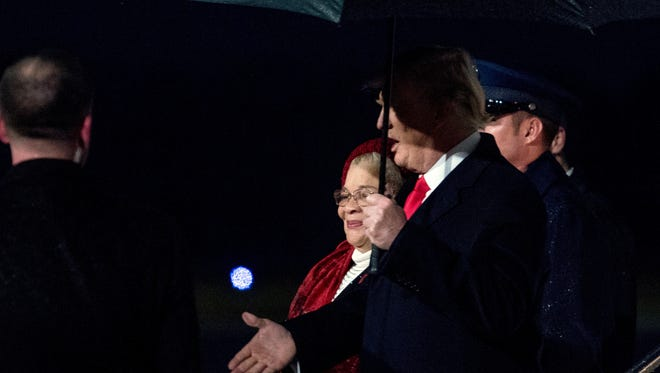 President Trump is  accompanied by Alveda King, niece of civil rights activist Martin Luther King Jr. as he arrives at Dobbins Air Reserve Base in Marietta, Ga., Monday. Trump signed a bill expanding the Martin Luther King national historical site before attending college football's national championship game in Atlanta.