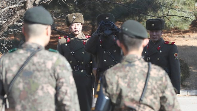 Three North Korean soldiers look at the South side as two South Korean soldiers stand guard at the spot where a defector crossed the border on Nov. 13, 2017.