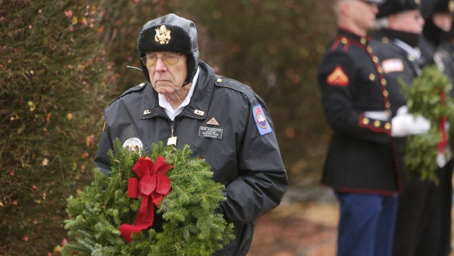 The Springfield National Cemetery hosted Wreaths Across America wreath-laying ceremony honoring and remembering our Nation's veterans. Bob Garoutte, with the Veterans Memorial Team honor guard places a wreath.