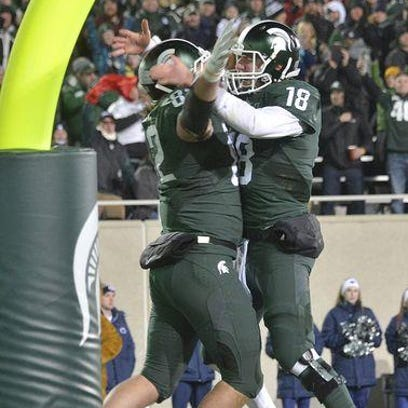 MSU's Connor Cook jumps into the air with tight end