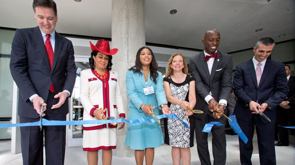 Dignitaries cut a ribbon to mark the dedication of the Federal Bureau of Investigation's new $194 million South Florida field office, on April 10, 2015, in Miramar, Fla. The office is named for agents Benjamin P. Grogan and Jerry L. Dove, who were killed in an April 11, 1986, shootout with heavily armed bank robbers south of Miami. Five other FBI agents were wounded in what remains the bureau's bloodiest single day. Three survivors attended Friday's ceremony. From left, FBI Director James Comey, U.S. Rep. Frederica Wilson, acting GSA Administrator Denise Roth, U.S. Rep. Debbie Wasserman Schultz, Miramar, Fla. Mayor Wayne Messam, and George Piro, Special Agent in Charge, FBI Miami.