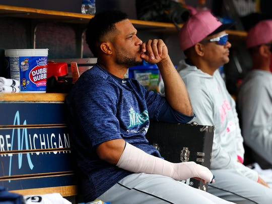 Seattle Mariners' Robinson Cano sits on the bench with his hand wrapped in the fifth inning of a baseball game against the Detroit Tigers in Detroit, Sunday, May 13, 2018. (AP Photo/Paul Sancya)
