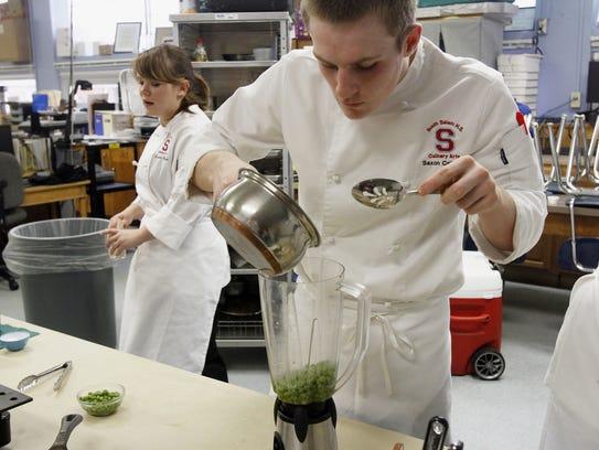 Ryan Toepfer prepares a pea cream sauce while practicing