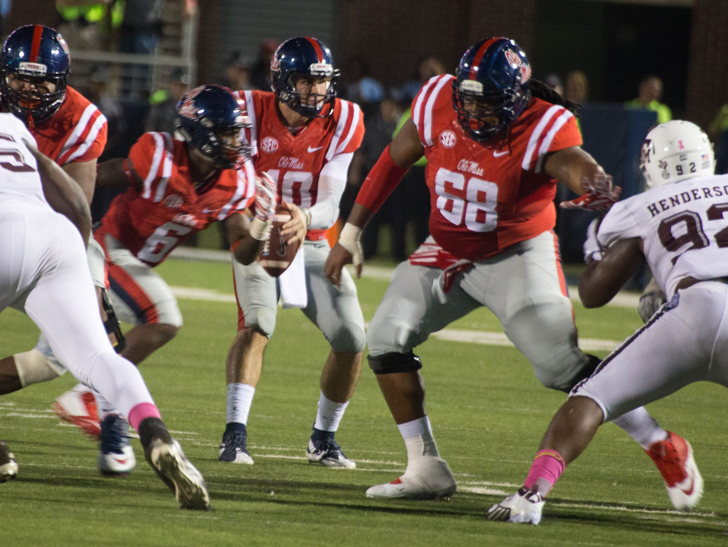 Former Callaway high school player Justin Bell hikes the ball and protects Chad Kelly from Zaycoven Henderson.