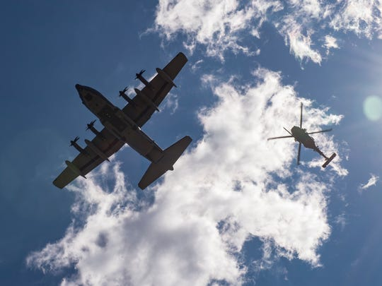 An HC-130J Combat King II and an HH-60G Pave Hawk fly over a formation of Airmen following a memorial service in honor of Capt. Mark Weber, March 21, 2018, at Moody Air Force Base, Ga. Rescue Airmen from the 23d Wing visited the Devil Raiders of the 621st Contingency Response Wing (CRW), May 21-23, to better understand the essential assets to stand up rescue operations from bare-base situations.