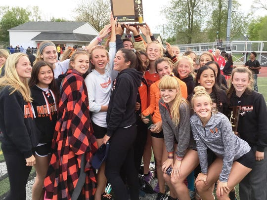 The Northville girls track and field team celebrate after winning their fourth straight Kensington Conference title.