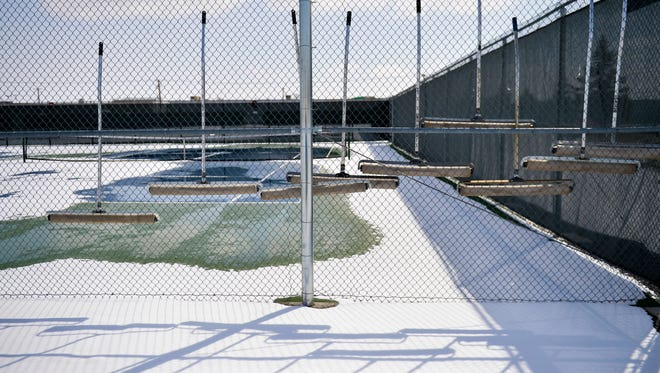Court squeegees hang neatly on the fence as the snow slowly melted on the CMR tennis courts last week. Another round of snowfall has put more local sporting events in jeopardy.