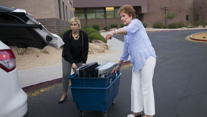 Elizabeth Bartholomew (left), communications manager for the Maricopa County Recorder's Office, and Maricopa County Recorder Helen Purcell bring a voting machine to a Republican district caucus in Phoenix April 6, 2016.