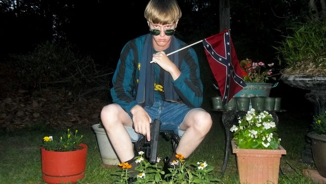 This undated image that appeared on Lastrhodesian.com, a website being investigated by the FBI in connection with Charleston, S.C., shooting suspect Dylann Roof, shows Roof posing for a photo while holding a Confederate flag.