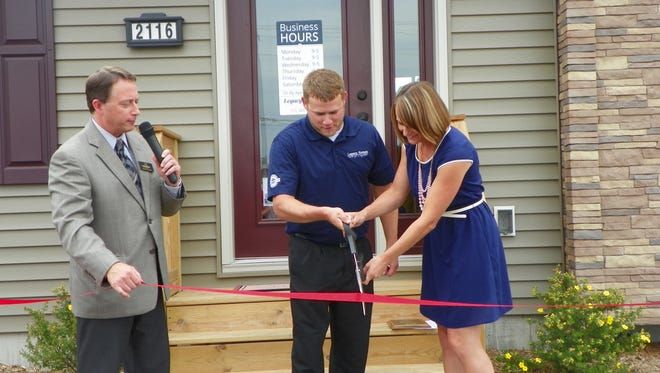 Marshfield Area Chamber of Commerce & Industry coordinated the ribbon cutting ceremony on Aug. 6 for Legacy Homes, 2116 N. Peach Avenue. Legacy Homes is the exclusive builder/dealer of Wisconsin Homes Inc. in central Wisconsin. The company first opened its doors in July of 2011 on the south end of Marshfield.  In fall of 2014, Legacy Homes moved to its new location on Peach Avenue (directly to the west of Menards).  Legacy Homes specializes in the design, planning, and construction of building Wisconsin Homes.  The owners of the company are Ben and Jenna Kautza, and currently employ one full-time salesperson. Pictured are  Ben and Jenna Kautza, at right, with Scott Larson, MACCI Executive Director.
