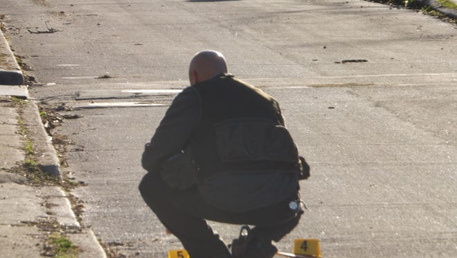 Detective Gerard Longnecker investigates evidence along South C Street after a report of shots fired Thursday morning in the 200 block of South Seventh Street.