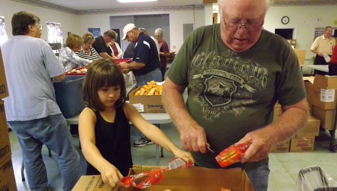 Chuck Winters and his granddaughter, Makenna Keeton, 8, both of Hagerstown, open packages of cheese crackers. They were placed in lunches assembled by volunteers behind them and given to children through the Backpack Blessing program.