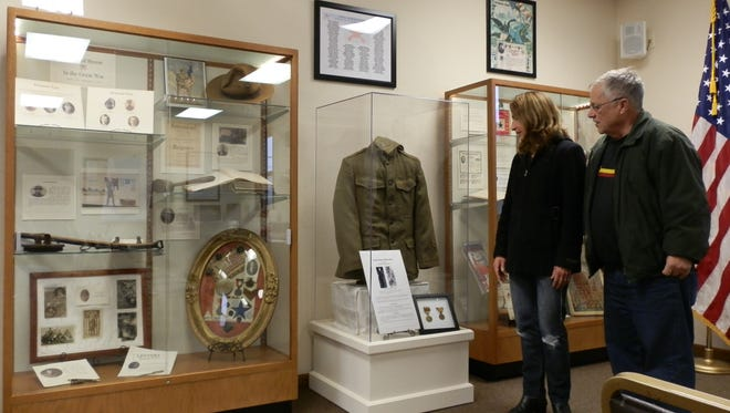 Evelyn McLean-Cowan and Mike Cowan examine local World War I memorabilia featured in the new Byron Historical Society exhibit properties.
