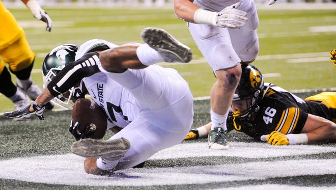 Michigan State defensive back Demetrious Cox (7) intercepts a pass in the end zone against Iowa.