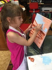 Young artist Maia Bastianelli of Pittsford does the underpainting and adds details for a work that will be auctioned Aug. 1, 2016.