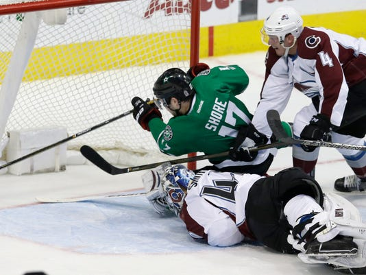 Dallas Stars center Devin Shore (17) gets the puck into the net scoring a goal against Colorado Avalanche goalie Jeremy Smith (40) and and defenseman Tyson Barrie (4) during the first period of an NHL hockey game in Dallas, Saturday, April 8, 2017. (AP Photo/LM Otero)
