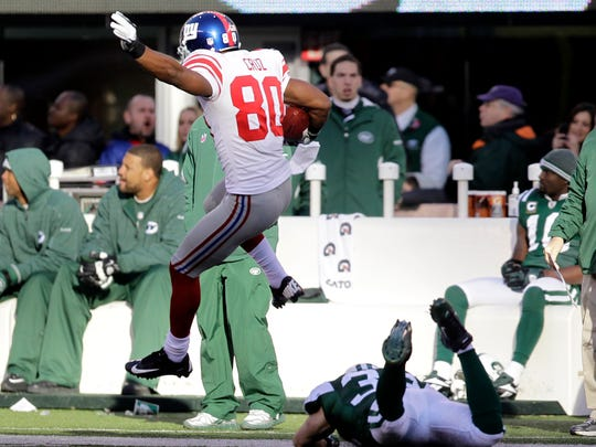 FILE- In this Dec. 24, 2011, file photo, New York Giants' Victor Cruz jumps over a New York Jets defender while scoring 99-yard touchdown during the second quarter of an NFL football game in East Rutherford, N.J. The Jets and Giants are preparing for their first regular-season showdown on Sunday, Dec. 6, 2015, since 2011. (AP Photo/Julio Cortez, File)