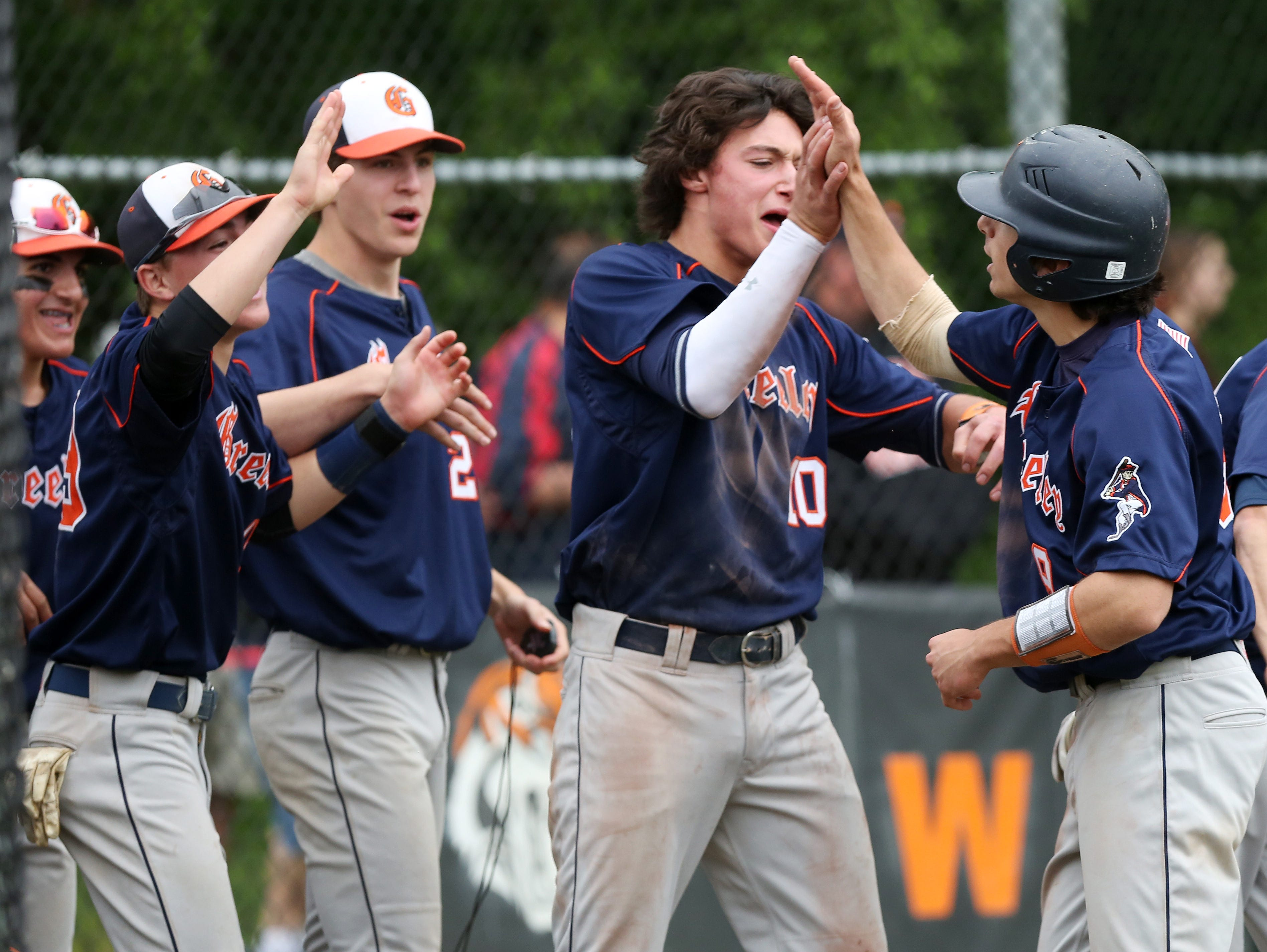 Horace Greeley's Nate Goodman, right, celebrates with teammates after scoring on Brandon Neeck's second-inning single against White Plains during a Section 1 playoff game at White Plains High School Saturday.
