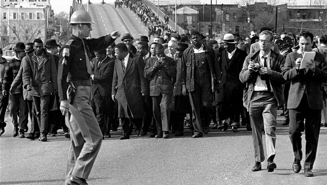 Demonstrators, including Dr. Martin Luther King, Jr., stream over the Edmund Pettus Bridge at the city limits of Selma, Ala., in this March 10, 1965 file photo, during a voter rights march.