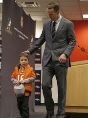 Denver Broncos quarterback Peyton Manning walks with his son, Marshall, after a press conference.