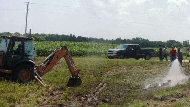 Manure spill cleanup takes place on Kewaunee County D and Wisconsin 54 in the aftermath of a tanker crash last summer.