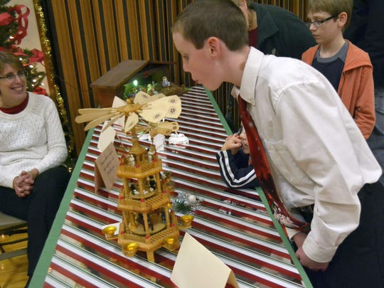"""Aaron Whitney, 12, of Pulaski, blows the spinning vanes atop a wooden Christmas pyramid from Germany. It was one of several nativity sets from around the world on display during the """"Christmas Creches, Carols and Choreography!"""" holiday event at The Church of Jesus Christ of Latter-day Saints in Green Bay."""