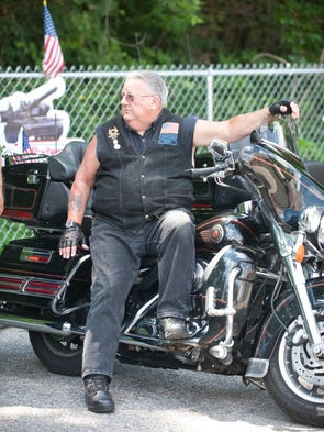 Roger Smith, a retired Jefferson County (Ky) police officer and member of the Guns of Justice (police officer) Motorcycle Club of Louisville, joins about 25 area police officers, veterans family members and friends in the first Purple Heart Ride which started at the Clarksville Veterans of Foreign Wars (seen here) and ended at Sellersburg's American Legion hall. The rode benefited the Wound Warrior Project  21 June 2014