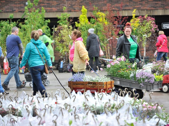 People walk between sheds during Flower Day at Eastern Market.