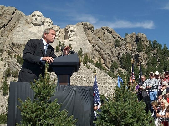 Watched by the faces of Mount Rushmore, President Bush