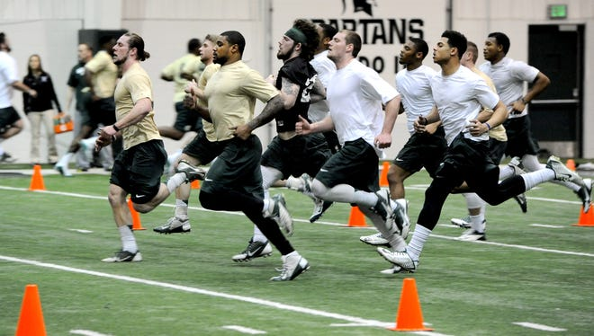 Riley Bullough, left, leads the linebacker squad as they run sprints during team conditioning in East Lansing on Tuesday, March 3, 2015.
