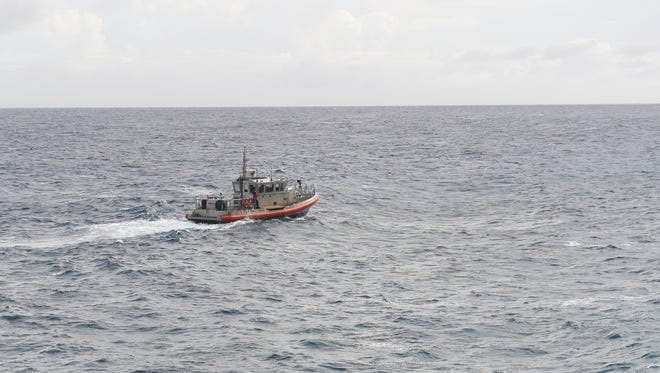 A U.S. Coast Guard tug boat patrols the waters near Pagat Point for a distressed swimmer on Nov. 20, 2016.